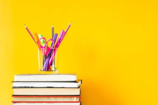 Um copo com canetas, lápis e tesoura em uma pilha de livros para treinamento