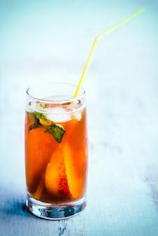 Um copo com chá de gelo caseiro, pêssego com sabor.