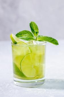 Um copo com chá matcha verde gelado com limão, gelo e hortelã no cinza.