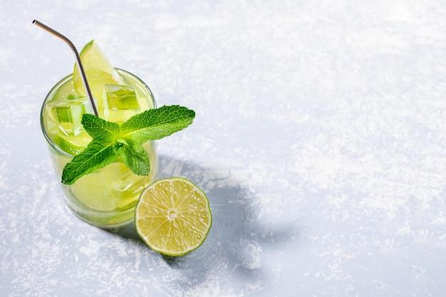 Um copo com chá verde matcha gelado com canudo de limão, gelo, hortelã e metal no cinza com espaço de cópia.