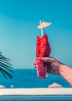 Um copo com fatias de melancia na mão de um homem no fundo do mar azul.