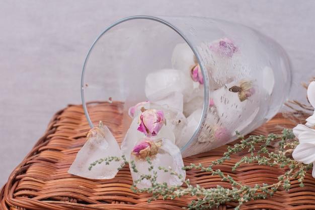 Um copo com gelo e pequenas rosas na superfície branca