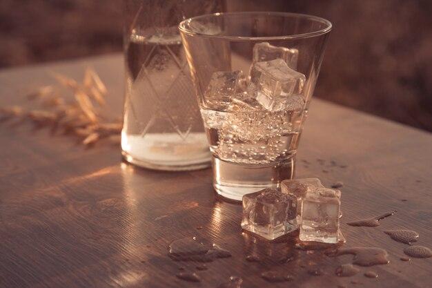 Um copo com gelo e pôr do sol na savana
