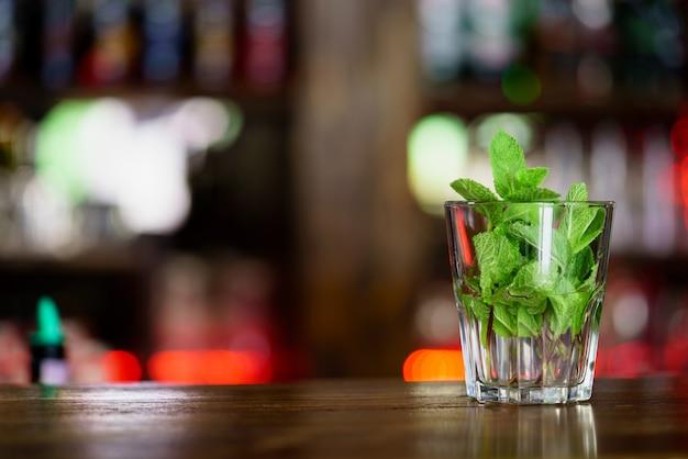 Um copo com hortelã fica no rack de madeira no bar