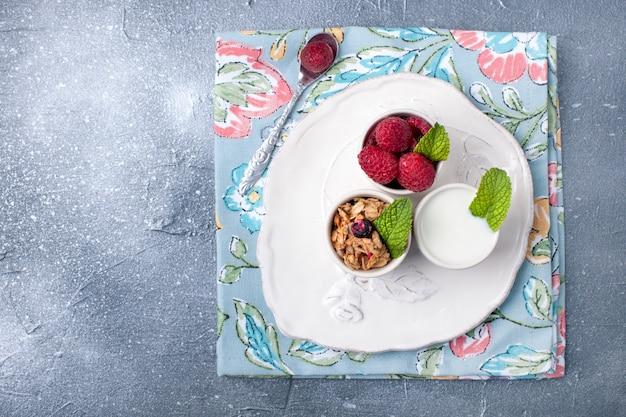Um copo com iogurte, cereais e frutas sobre um fundo cinza e um prato branco