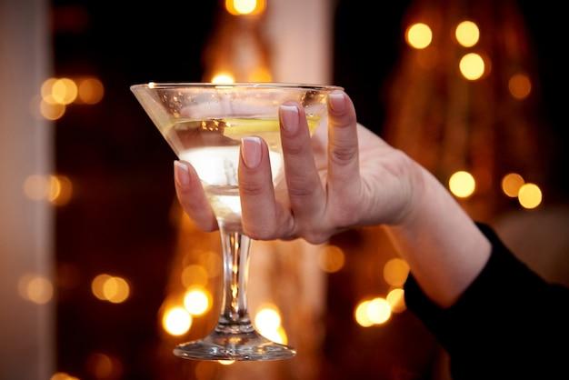 Um copo com martini em uma mão feminina em um fundo escuro com bokeh.