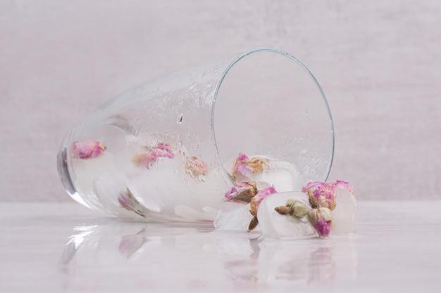 Um copo com pequenas rosas em gelo na mesa branca.