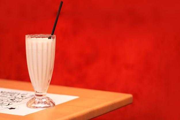 Um copo com um batido em uma mesa em um café no fundo de uma cadeira vermelha