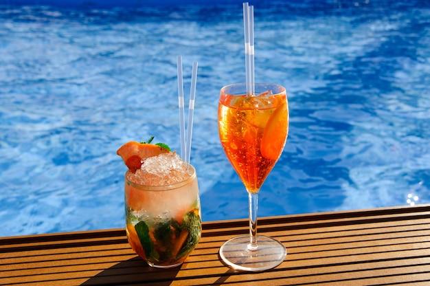 Um copo com um coquetel de laranja perto da piscina