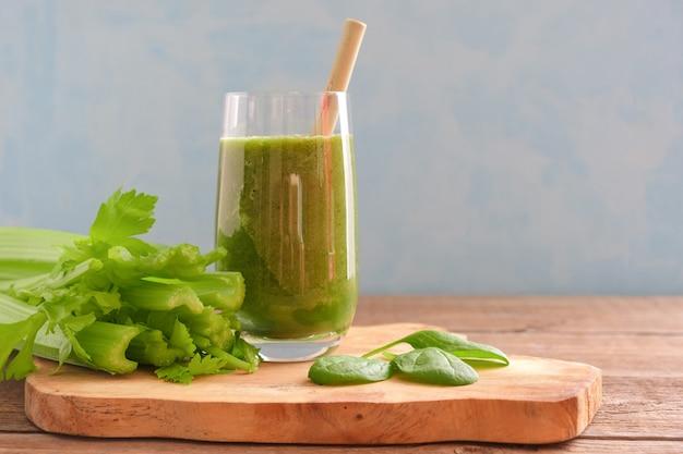 Um copo com um smoothie verde e um canudo de bambu de coquetel está em uma placa de madeira.
