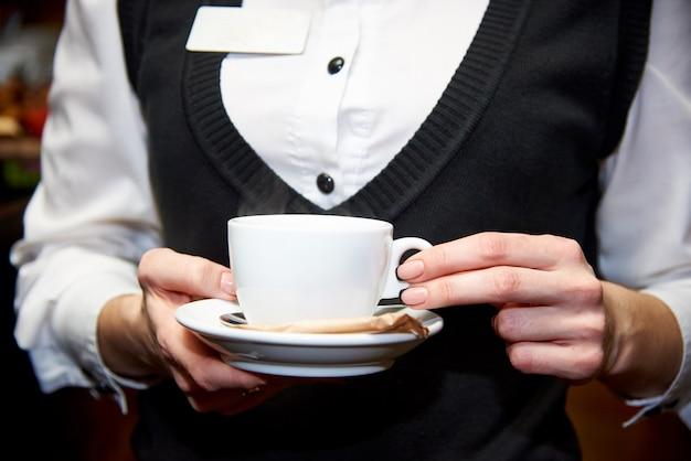 Um copo com uma bebida quente em um pires nas mãos de um garçom de uniforme