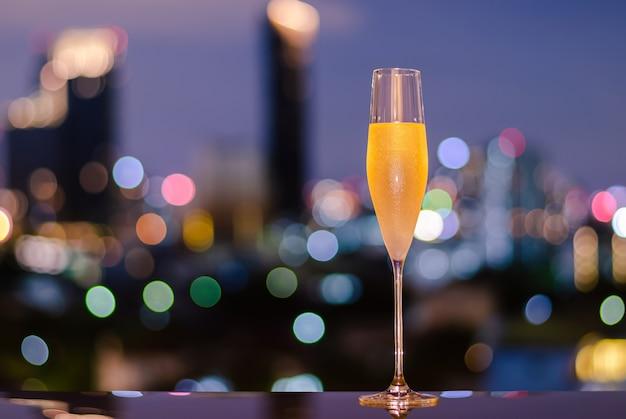Um copo com vapor de champanhe gelado na mesa com luzes coloridas do bokeh da cidade