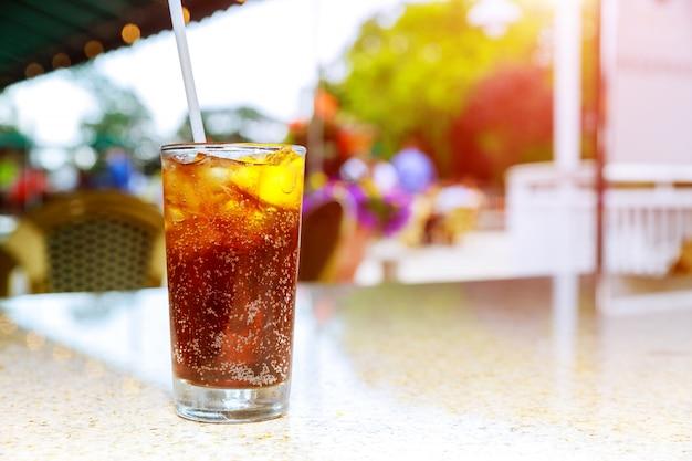 Um copo contendo uma bebida alcoólica em uma mesa de um terraço de um bar