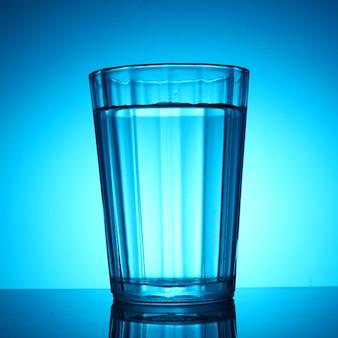 Um copo d'água em um fundo azul
