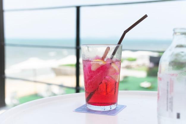 Um copo de água com bebida vermelha na mesa branca