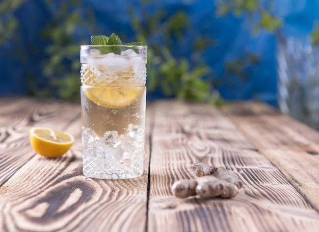 Um copo de água com gás fresca com gengibre, limão e gelo
