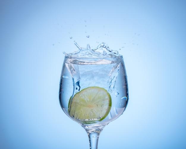 Um copo de água com limão caiu e respingos no fundo gradiente azul claro.