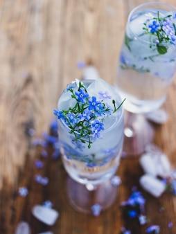 Um copo de água e cubos de gelo com flores