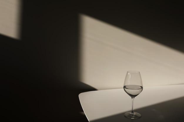 Um copo de água em um fundo branco com uma sombra claro do claro-escuro da janela closeup cópia espaço