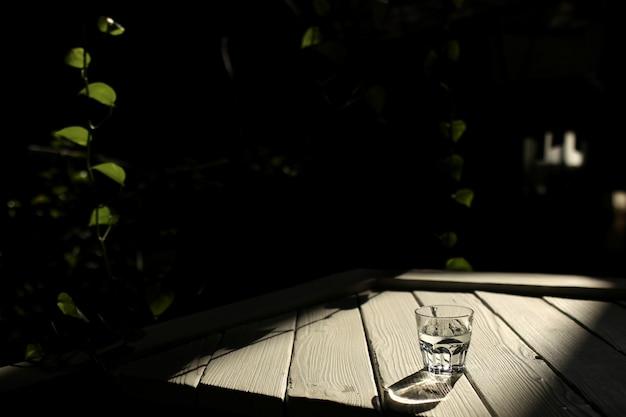 Um copo de água em uma mesa branca com raios de sol com fundo de natureza