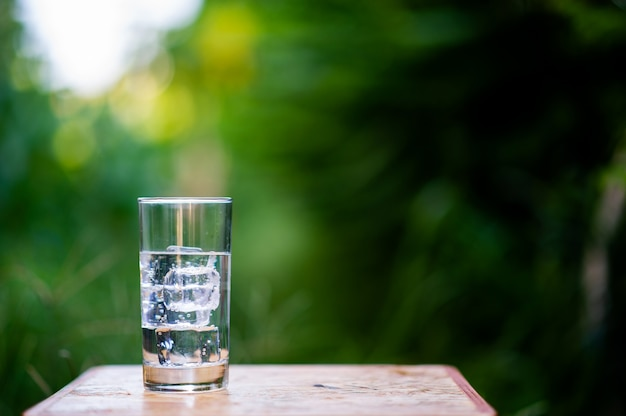 Um copo de água limpa com gelo colocado sobre a mesa, pronta para beber