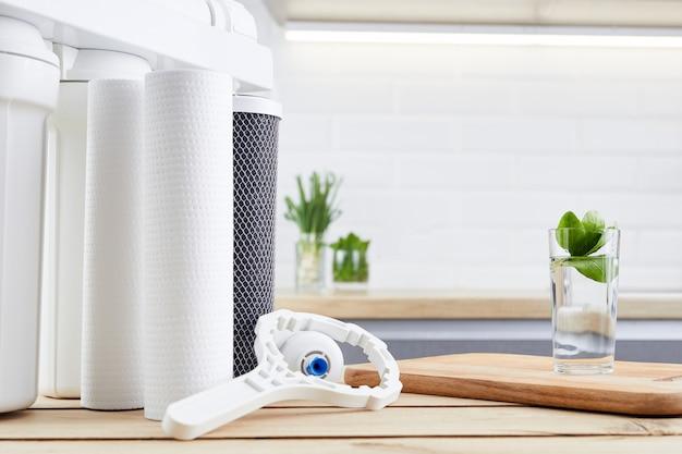 Um copo de água limpa e cartuchos de filtro na cozinha de casa