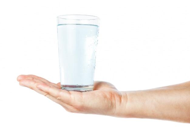 Um copo de água limpa e fresca na mão do homem. em uma parede branca.
