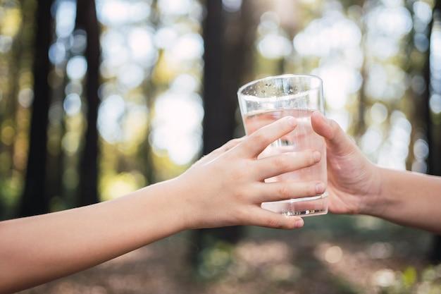 Um copo de água potável é passado de mão em mão - conceito do dia mundial da água