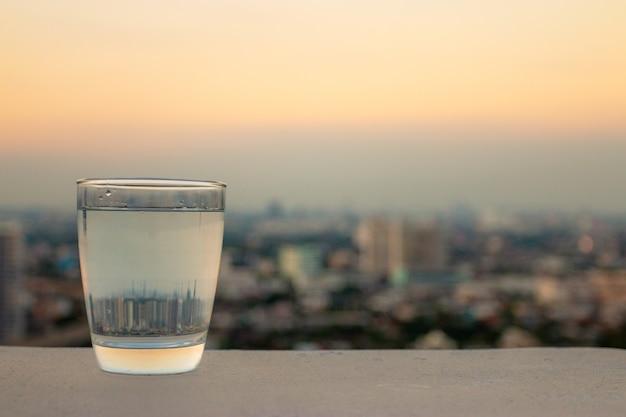 Um copo de água potável em um fundo de cidade turva, o conceito de saúde.