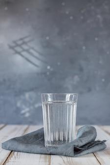 Um copo de água potável em um guardanapo em uma mesa de madeira. o conceito de um estilo de vida saudável.