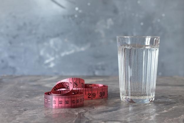 Um copo de água potável em uma mesa de mármore em um fundo desfocado cinza. ao lado dele é um centímetro.