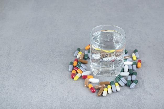 Um copo de água pura com pílulas coloridas na superfície cinza