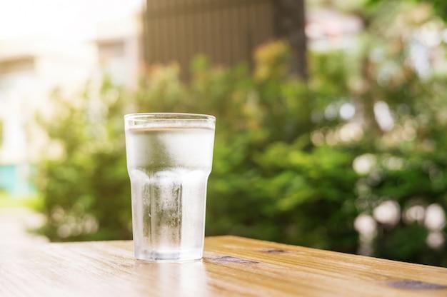 Um copo de água sobre uma mesa de madeira.