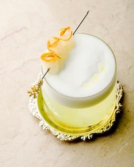 Um copo de bebida com espuma dentro da bandeja decorativa.
