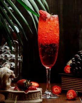 Um copo de bebida com gás de morango guarnecido com morangos