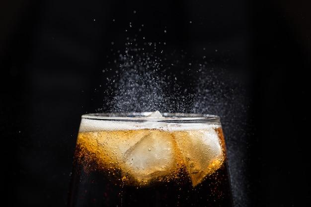 Um copo de bebida de cola com um close-up de sal.