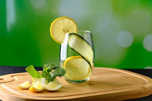 Um copo de bebida de limão siciliano em uma placa de madeira isolada em um fundo verde