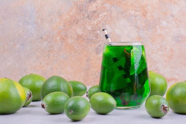 Um copo de bebida verde com feijoa e tangerinas