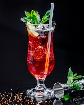 Um copo de bebida vermelha com folhas de hortelã e cachimbo.