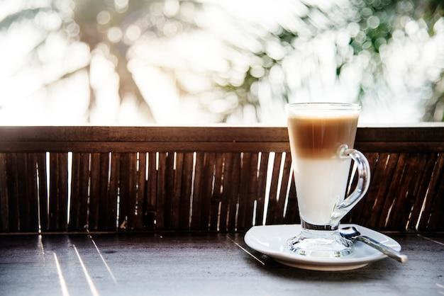 Um copo de café com leite à beira da praia