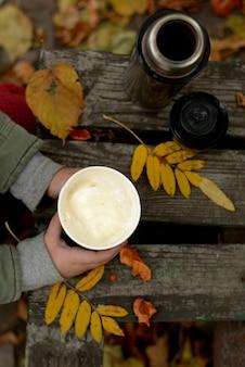 Um copo de café com leite delicioso com espuma leitosa nas mãos de uma criança. tempo de outono.