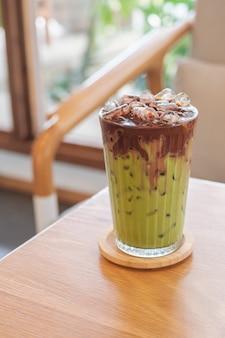 Um copo de café com leite gelado fusão duas camadas de matcha e chocolate na mesa de madeira, refresco de latte caseiro