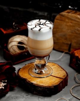 Um copo de café com leite quente com espuma em um cânhamo de árvore