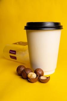 Um copo de café com nozes de macadâmia em um fundo amarelo