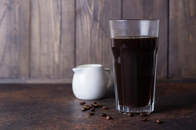 Um copo de café expresso quente com grãos de café