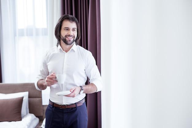 Um copo de café. homem de negócios alegre e positivo sorrindo enquanto saboreia sua bebida matinal