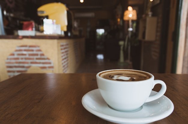 Um copo de café na tabela de madeira na cafetaria e no espaço da cópia.