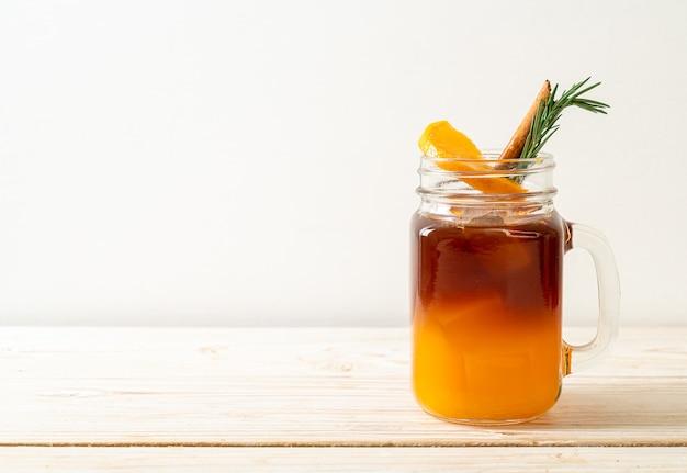 Um copo de café preto americano gelado e uma camada de suco de laranja e limão decorado com alecrim e canela em fundo de madeira