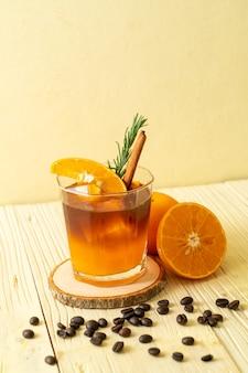 Um copo de café preto americano gelado e uma camada de suco de laranja e limão decorado com alecrim e canela