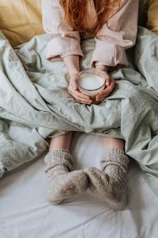 Um copo de café quente com espuma de leite, que a menina segura nas mãos, sentada em meias quentes na cama.